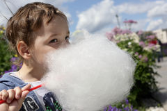 Kid licks cotton candy Royalty Free Stock Image