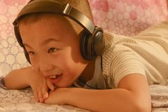 Kid  lie prone enjoying music Stock Images