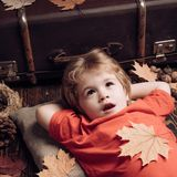 Kid lies laying his hands behind head and resting on wooden floor in golden leaves. Autumn concept. Kid having fun with royalty free stock photography