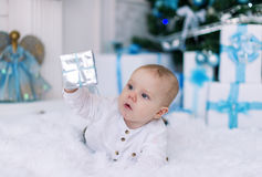 The kid lies on a white bed with gifts by Christmas. Royalty Free Stock Photography