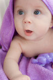 The kid in a lilac towel looks the surprised sight Royalty Free Stock Image