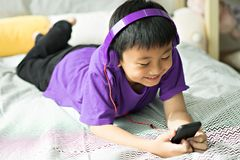 Kid listening to music on bed in bedroom stock image