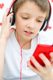 Kid listening to the music. Cute little girl smiling listening to the music on smart phone mobile device with headphones Royalty Free Stock Images