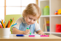 Kid little boy paints in his nursery at home Royalty Free Stock Images