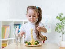 Kid little girl eats vegetarian food at home or kindergarten Royalty Free Stock Photo