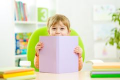 Kid little girl hiding behind book stock photo