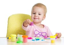 Little girl learning to use colorful play dough  on white background. Kid little girl learning to use colorful play dough  on white background Royalty Free Stock Photos
