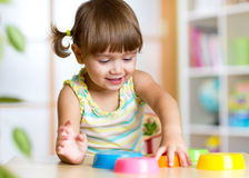 Kid little girl playing with toys indoors Royalty Free Stock Images