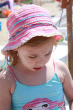 Kid with little injury on his face. Pink beach hat Royalty Free Stock Images