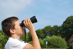 Kid is looking through binoculars Royalty Free Stock Images