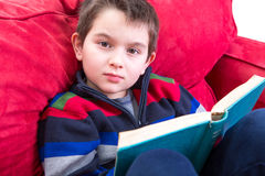 Kid Reading Book on the Couch. Kid looking at camera while reading a book on the red couch. He has a meaningful look on his face, perhaps distracted Stock Images