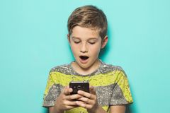 Child looking at a cell phone with a surprised look on his face stock photos