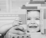 Kid looking through door of toy house made of blocks. Kid looking through door of toy house made of plastic blocks. Child with smiling face plays with stock photography