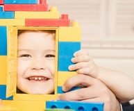 Kid looking through door of toy house made of blocks. Kid looking through door of toy house made of plastic blocks. Child with smiling face plays with stock images