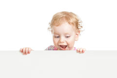 Kid looking down behind white emty banner. On white background royalty free stock image
