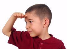 Kid looking far off with eyes shaded. Eight year old boy looking at a distance with hand shielding his eyes, isolated on white background Stock Image