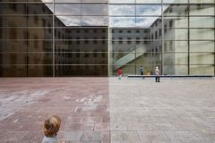 Kid looking at a group playing. A kid looking at another group playing and dancing in front of a a modern glass façade. The building is a Museum in Barcelona stock image