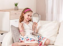Kid looking on her image with new accessories stock photography