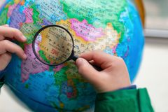 Kid looking at the map of China on a globe with magnifier stock images
