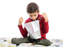 Kid looking for toy in shopping bag Stock Image