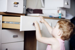Kid looking for trouble. Motion blur of little child searching  trough a drawer all by himself Stock Image