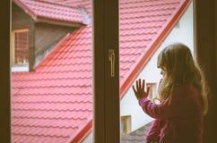 Kid looking through window. Girl with long hair looking through window Stock Image