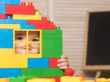 Kid looking through window of toy house made of blocks. Kid looking through window of toy house made of plastic blocks. Boy holds toy house on light background stock photos