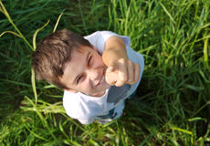 Kid looks up pointing to camera Stock Image
