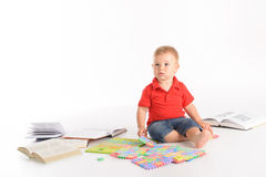 Kid with lot of books and letter puzzles Stock Photos