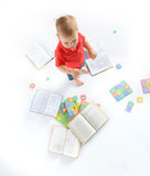 Kid with lot of books and letter puzzles Royalty Free Stock Photo