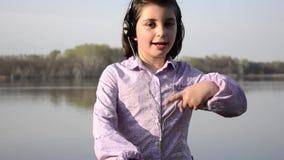 Kid loving music near a lake stock video footage