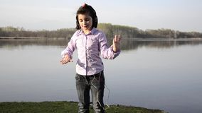 Kid loving music near a lake stock video
