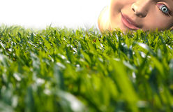 A Kid Lying Down On Grass Looking Inquisitively Royalty Free Stock Photography