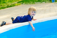 Kid lying down by the pool Royalty Free Stock Photo