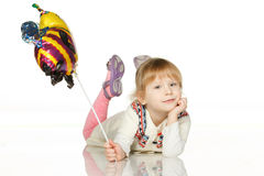 Kid lying on the floor with balloon bee Royalty Free Stock Image