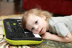 Kid lying and playing on synthesizer Stock Images