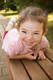 Kid lying on wooden park bench Stock Image