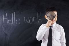 Kid with magnifier and text Hello World Stock Image