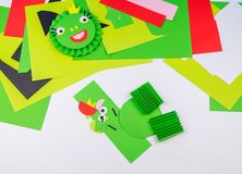 Kid makes a frog out of paper stock image