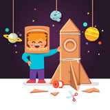 Kid making cardboard box rocket, astronaut costume Royalty Free Stock Image