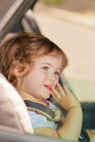 Kid making faces sitting in car safety seat Royalty Free Stock Images