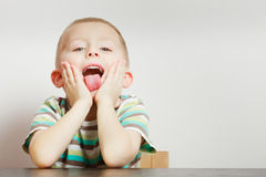 Kid making funny faces being bored. Boredom, face expression concept. Little boy making funny faces being bored, he wants to play with somebody Stock Photography
