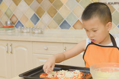 Kid making pizza. Chinese kid making pizza in kitchen royalty free stock photo