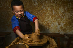 Kid making pottery. Chinese happy kid making pottery, playing professional worker stock image