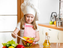 Kid making salad at kitchen Royalty Free Stock Image