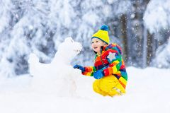 Child making snowman. Kids play in snow in winter stock images