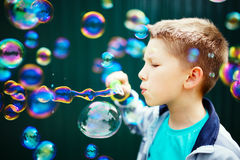 Kid making soap bubbles. Outside Stock Images