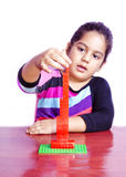 Kid making tower with blocks. A kid is finishing block tower modal Royalty Free Stock Images
