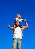 Kid on man's shoulders with thumbs up. Smiling kid on his man's shoulders with thumbs up Royalty Free Stock Photo