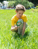 Kid on the meadow looking the grass with a magnifying glass.
